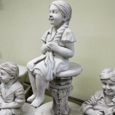 Betonipatsas, istuva tyttöpatsas, kuvattu sivulta
