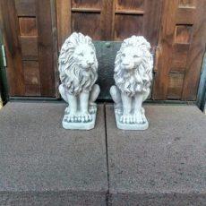 Leijonapatsaat, betonipatsaat pihalle, kuvattu vierekkäin