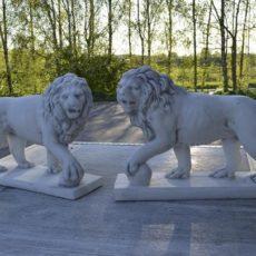 Leijonapatsaat, kaksi betonipatsasta, kuvattu vastakkain pihalla