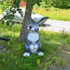 Pupupatsas, istuu puun vieressä